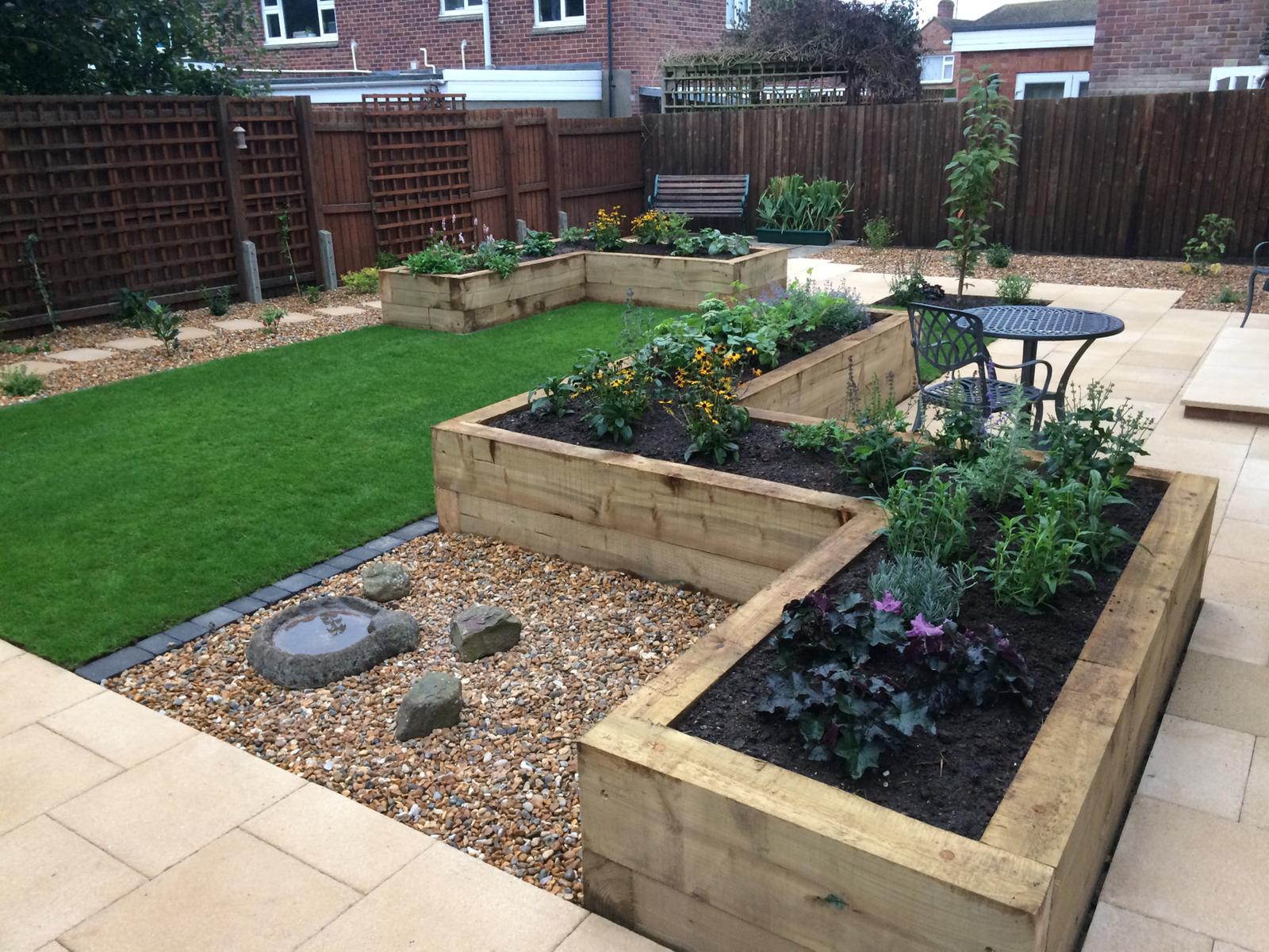 Creative landscaping with raised borders - Landscaping with summer house and pond - Period front garden - Grey slabs with raised beds - Landscaping large garden - Landscapes portfolio by Martyn Powell Landscapes in Cheltenham